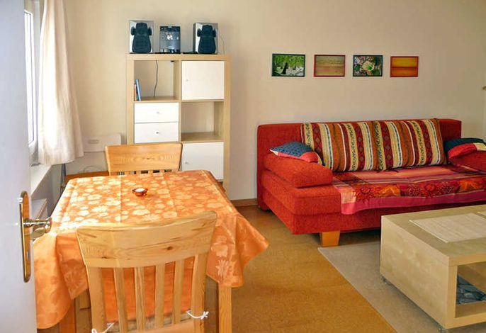 Wohnraum mit Schlafsofa, TV und Esstisch