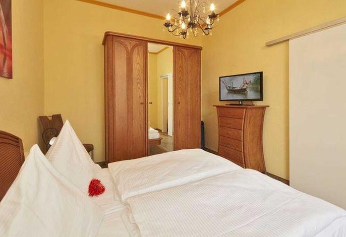 Schlafzimmer mit Doppelbett und zweitem Flachbildfernseher