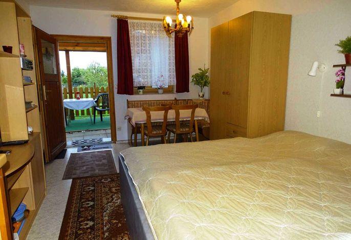 Wohn-/Schlafzimmer mit Doppelbett und Sitzecke und Küchenzeile