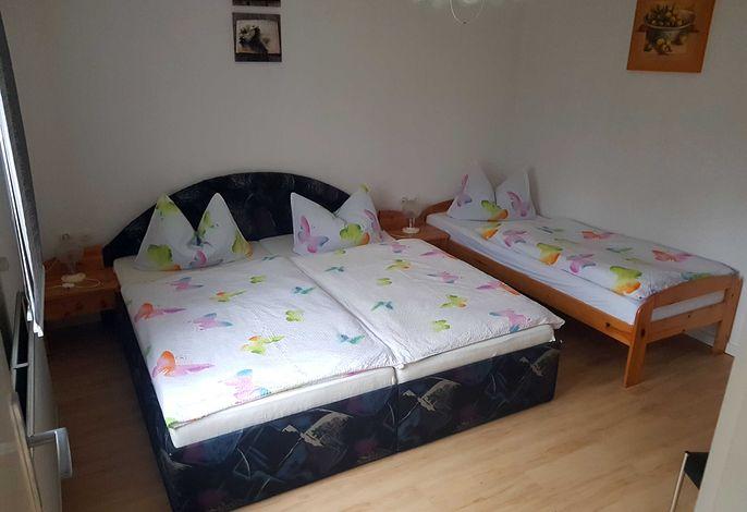 Schlafzimmer mit einem Doppelbett und einem Einzebett