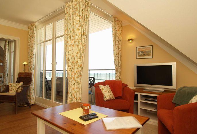 Das Wohnzimmer mit Sitzecke und Zugang zum Balkon zur Seeseite mit Meerblick