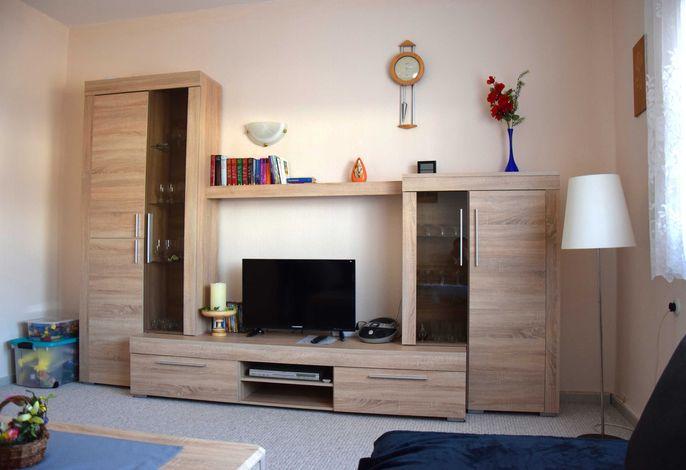 Wohnzimmer mit Schrankwand und Sat-TV