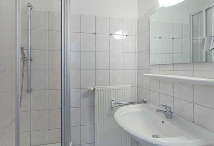 Bad mit Dusche und Waschbecken.