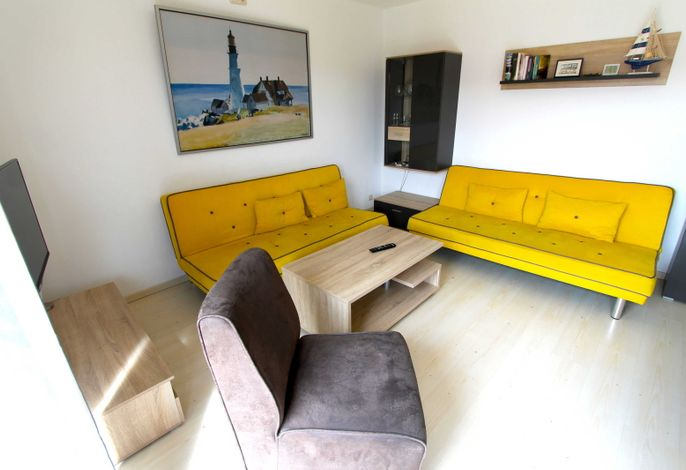 kombinierter Wohnraum mit zwei Schlafcouchen, Essbereich und Küchenzeile