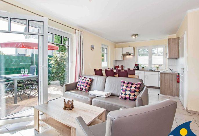 Wohnzimmer mit Essbereich, Küchenzeile und Zugang zur Terrasse