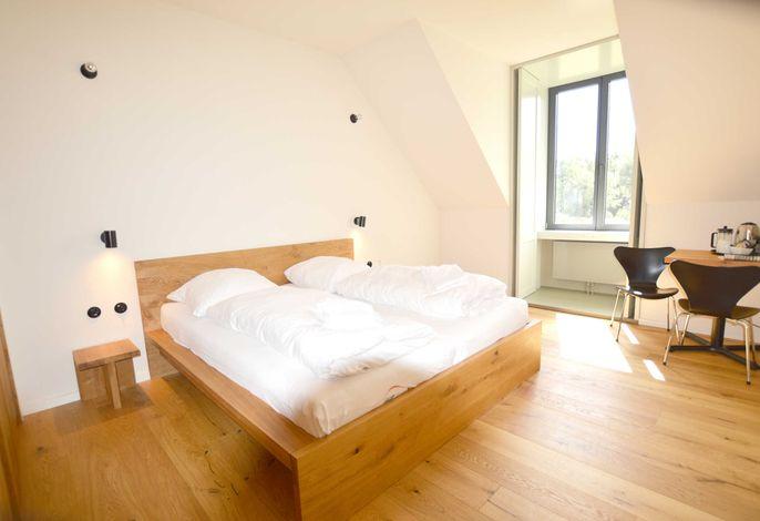 Gästezimmer mit Doppelbett, Bad und Tisch mit Stühlen