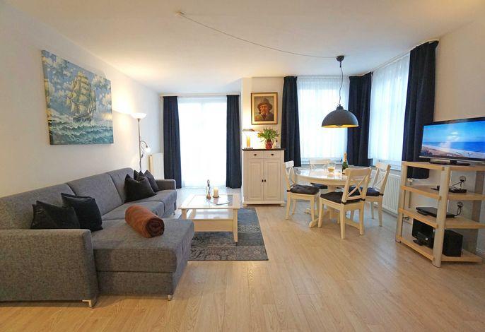 geräumiges Wohnzimmer mit Schlafcouch, Esstisch und Flachbildfernseher