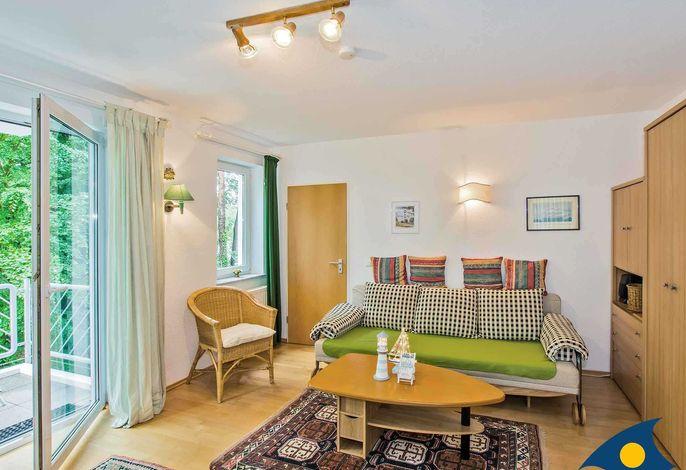 Wohnzimmer mit Schlafcouch und Zugang zum Balkon