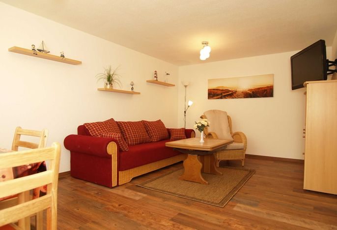 Der Wohnbereich mit gemütlicher Couchgarnitur, Essecke und TV