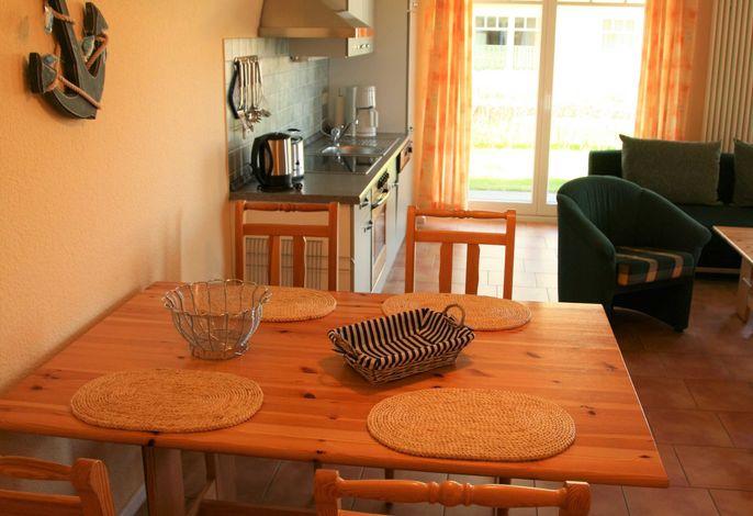 Wohnraum mit offener Küche und Zugang zur Terrasse