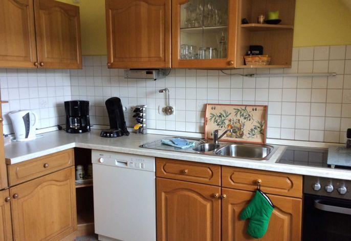 Küche mit Geschirrspülmaschine und Elektroherd