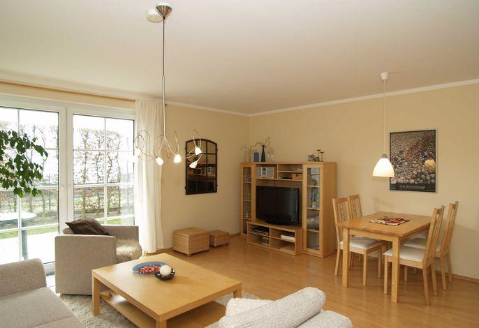 Der Wohnbereich mit Sitzecke, Flachbild-TV, Essecke und Zugang zur möblierten Terrasse