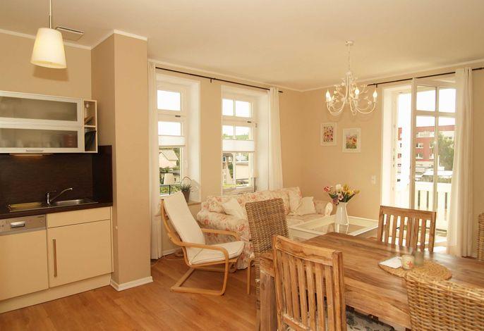 Der Wohnbereich mit gemütlicher Couchgarnitur, Essecke und Zugang zum Balkon