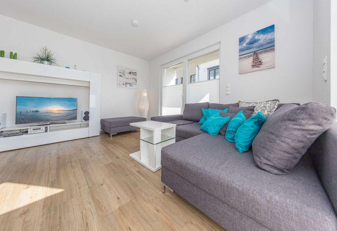 Komfortable Couchgarnitur und Flatscreen-TV im Wohnbereich