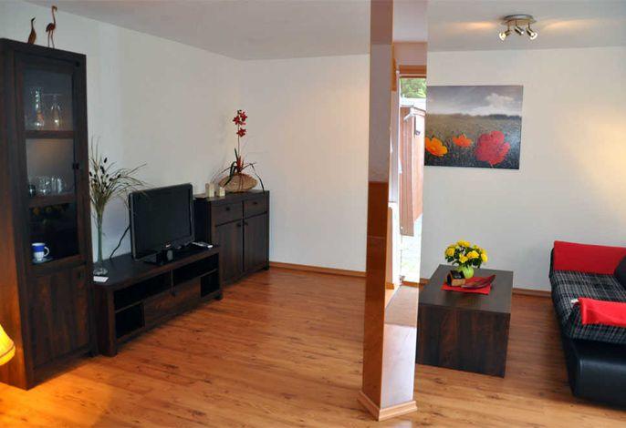 Wohnzimmer mit Couch und Flachbild-TV