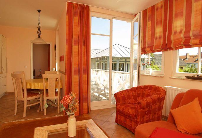Der Wohnbereich mit Sitz- und Essecke sowie einem Zugang zum möblierten Balkon