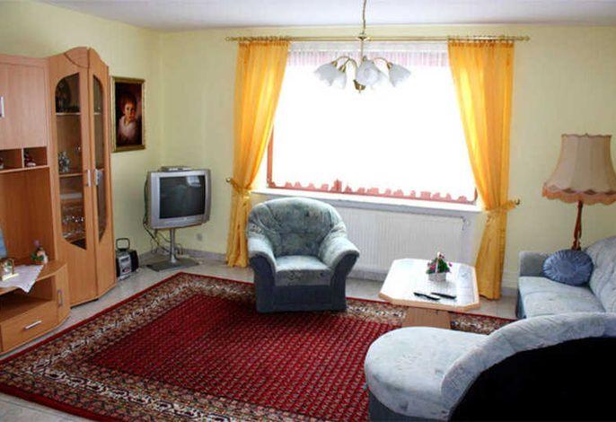 Wohnzimmer mit TV und Polstermöbeln