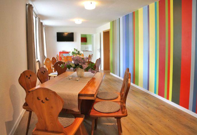 Farbenfroher Gruppenraum im Haus Strandgut (EG) für gemeinschaftliche Mahlzeiten, Spieleabende usw.