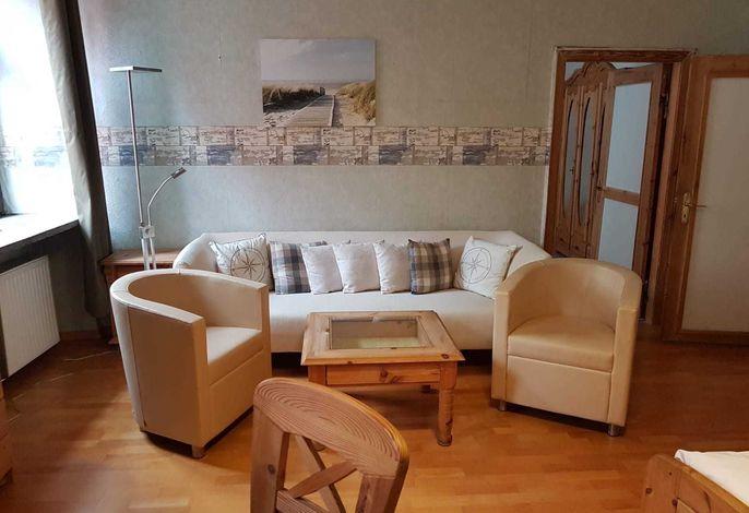 Wohnzimmer mit Doppelbett und Sitzgarnitur