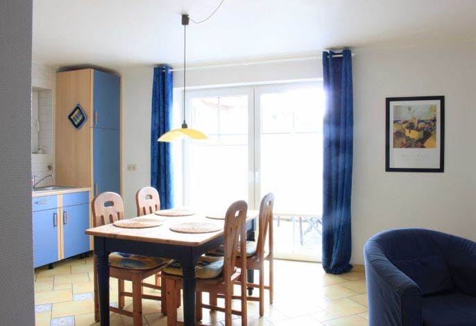 Kombinierter Wohn-/Essraum mit hellem Essplatz am Fenster.