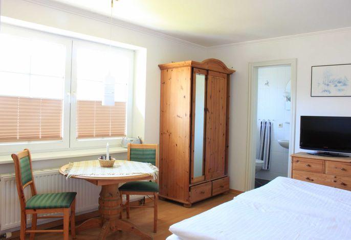 Der kombinierte Wohn-/Schlafraum mit gemütlichem Essplatz am Fenster.