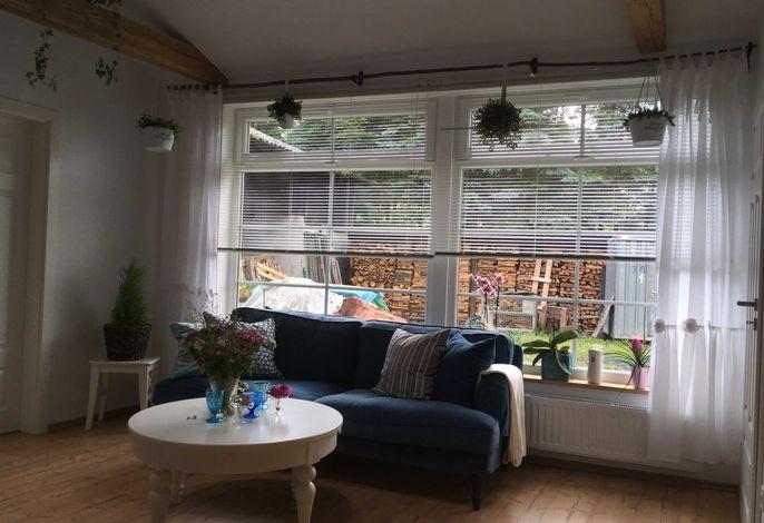 Wohnzimmer mit 3er Sofa und Lesesessel und LED Flachbildfernseher