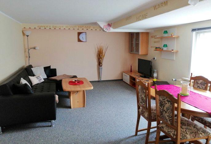 Geräumiges Wohnzimmer mit Couch und Flat-TV