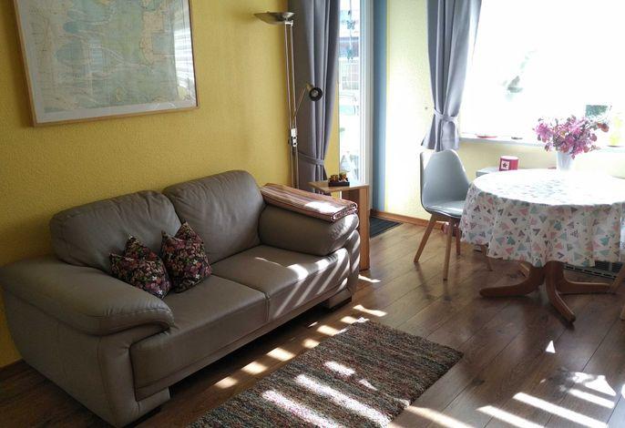 Wohnzimmer mit gemütlicher Couch und Essecke