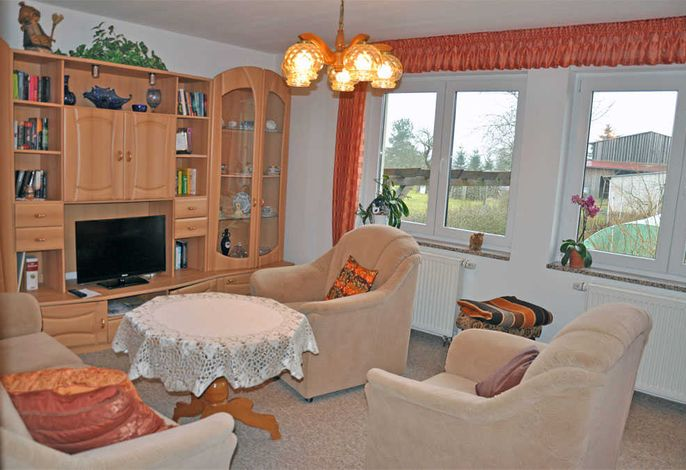 Wohnzimmer mit Schlafcouch und Flachbild-TV