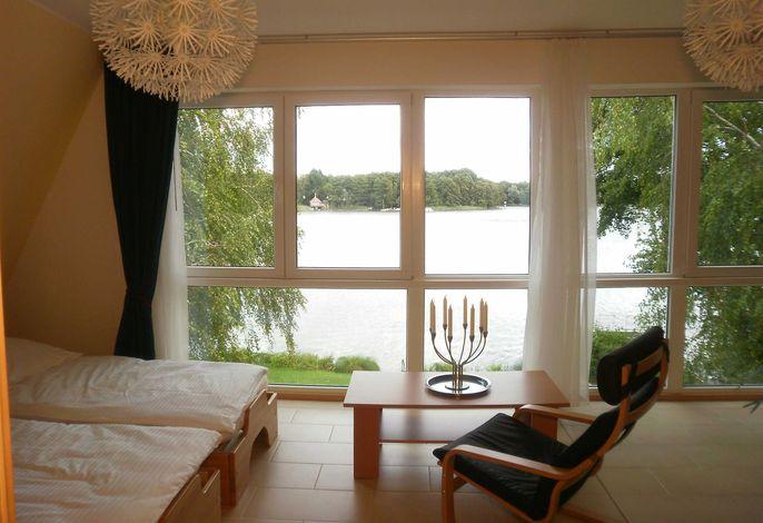 Der Wohnbereich im kombinierten Wohn-, Schlafraum mit weiter Aussicht auf den See.