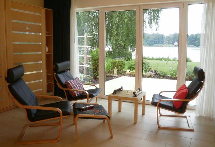 Der Wohnbereich im kombinierten Wohn-, Schlafraum mit Aussicht auf den See.