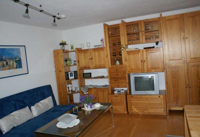 Wohnzimmer mit Wandschrank, CD Player, Fernseher, Esstisch, Sofa, ausziehbarer Schlafsessel