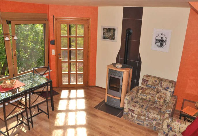 Wohnzimmer mit Kamin und Zugang zur Terrasse