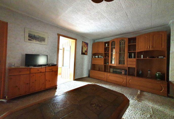 Wohnzimmer mit einer kleinen Couch, Schrankwand und TV