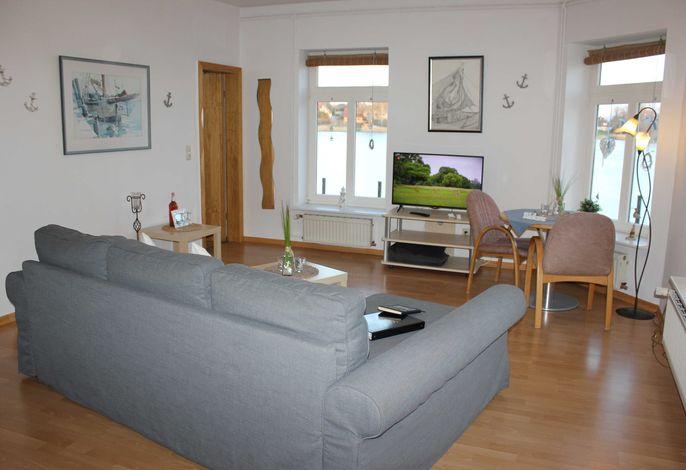 großes Wohnzimmer mit Fernseher und Essbereich