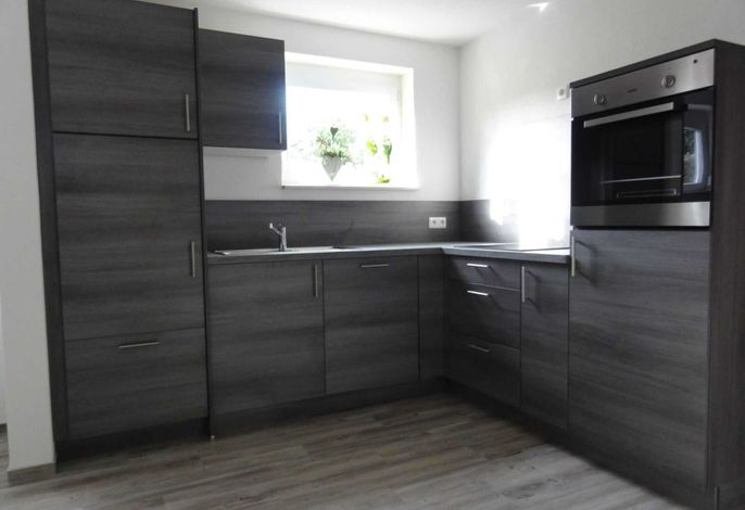 Küche mit Kühlschrank, Spülmaschine, Backofen, Herd