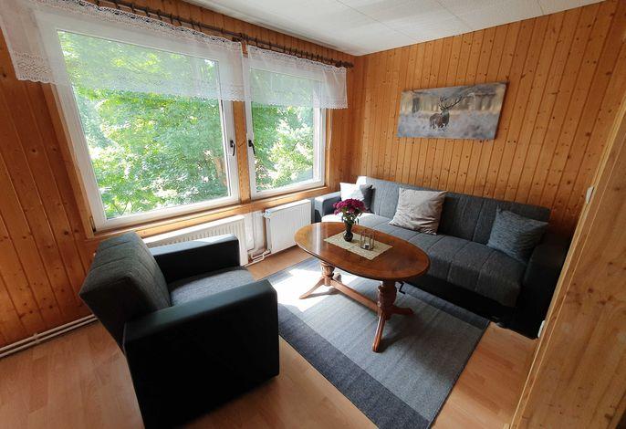 Helles und freundliches Wohnzimmer mit großen Fenstern und einer Schlafcouch