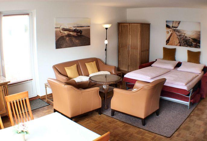 Links sieht man die Terrassentür, vorne den Esstisch und hinten die gemütliche Sitzecke mit ausgeklapptem Schlafsofa.