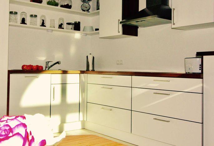 Küche mit Spülmaschine, Cerankochfeld, Kühlschrank mit Gefrierfach, Toaster, Kaffeemaschine, Pad-Kaffee-Maschine, Wasserkocher, Backofen und Mikrowelle.