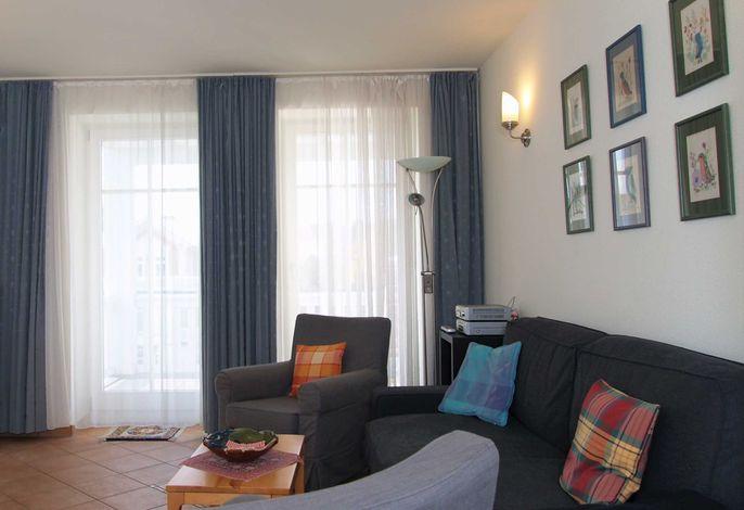 Das Wohnzimmer mit gemütlicher Sitzecke und Zugang zum Balkon