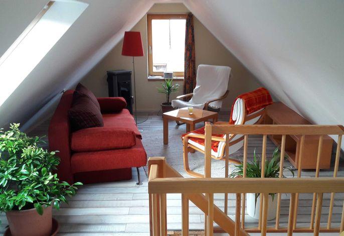 offener Wohn- und Schlafraum mit Kamin im Dachgeschoss