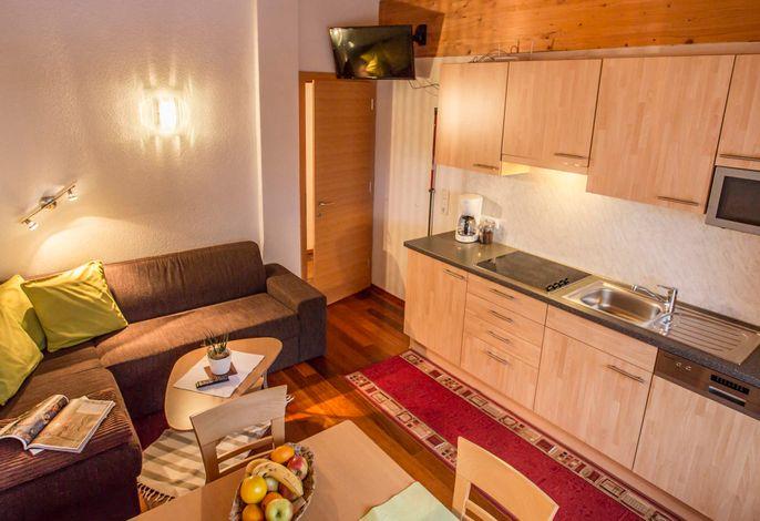 Wohnküche mit gemütlichem Ecksofa und TV