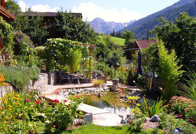 Terrasse am Gartenteich mit großem Sonnenschirm und Grillmöglichkeit.