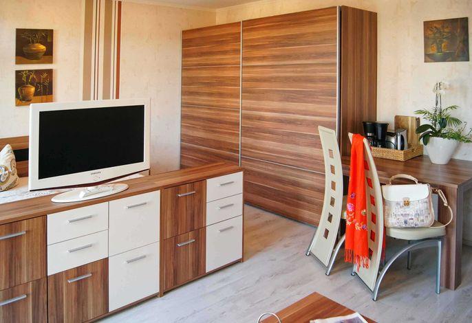 Wohnzimmer mit Esstisch und Schrank
