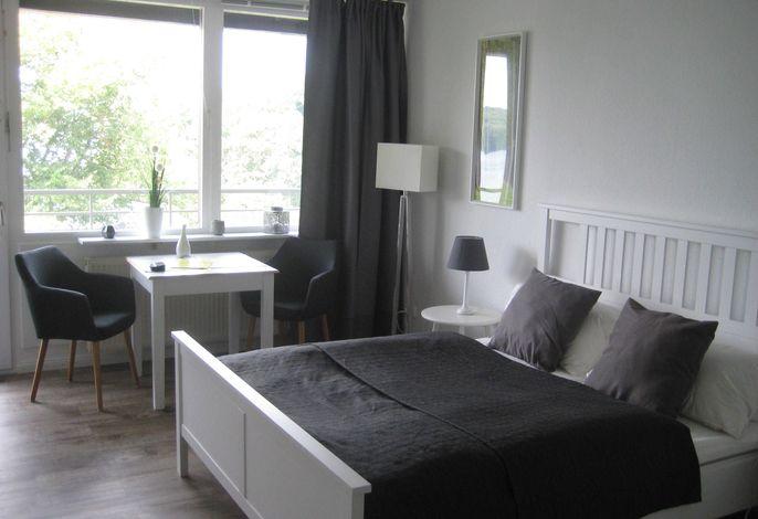 Wohnzimmer mit Doppelbett und Sitzgelegenheit