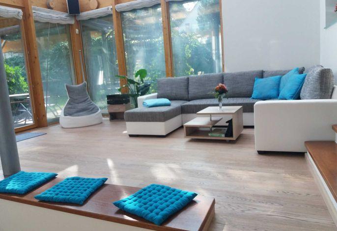 Wintergarten unten mit Sitzbereich um den Kamin mit Flachbild- TV und Couch