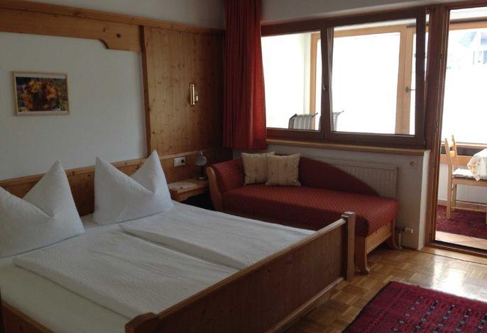 Schlafzimmer mit Couch und Wintergarten/Loggia mit Essecke und Liegestühlen