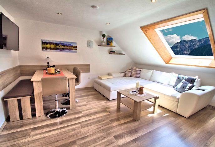 Wohnbereich mit einer gemütlichen Couch, Flachbild-TV, Küchenzeile und Essbereich, Kinderhochstuhl und eine gut ausgestattete Küche .