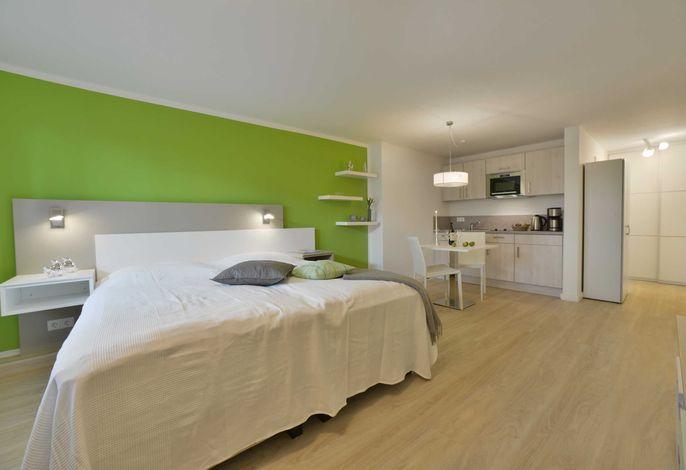 Wohnbereich mit Doppelbett und Küche und Essbereich