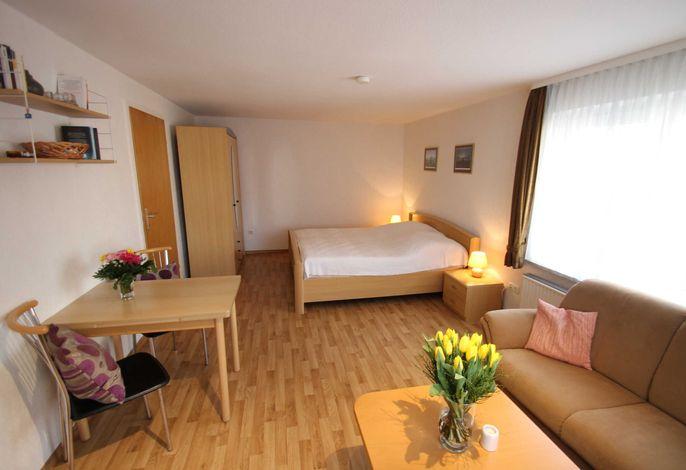 Wohnbereich mit Doppelbett im hinteren Zimmerbereich